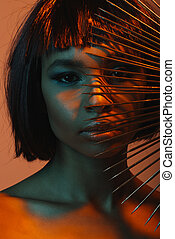 close up portrait of young attractive african american girl with dangerous needles