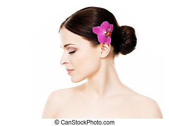 Close-up portrait of young, beautiful and healthy woman with an orchid flower in her hair isolated on white