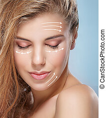 Close-up portrait of young, beautiful and healthy woman with arrows on her face.
