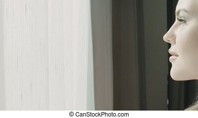 Close up portrait of young blonde woman near the window in hotel room
