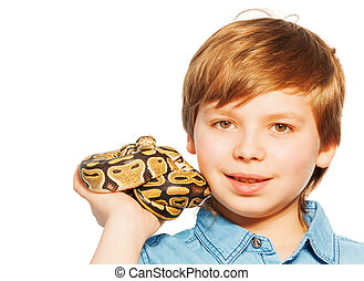 Close-up portrait of young boy with Ball python - Close-up...