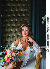 Close-up portrait of young bride posing with gorgeous bridal bouquet on a sofa