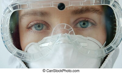 Close-up portrait of young girl doctor in safety suit goggles and respirator standing alone on white background and looking at camera. People and job concept.