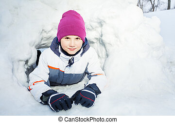 Close up portrait of young kid playing in the snow