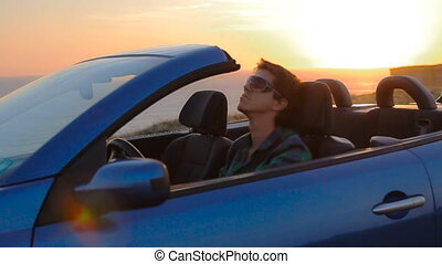 Close up portrait of young man relax in cabriolet, on the beach above the sea. Handsome guy at sunset