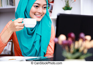 young muslim woman enjoy drinking a cup of tea