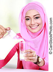 young muslim woman pouring milk into a glass