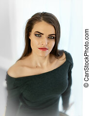 Close-up portrait of young pretty female 20-30 years old dressed in a feminine sexy dress with an open neckline standing next to window with white curtains