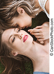 close up portrait of young sensual homosexual couple lying on the grass