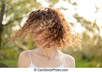 Close up portrait of young smiling attractive woman with curly hair in green flowering spring park. Pure emotions.