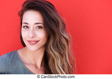 young smiling woman against red background