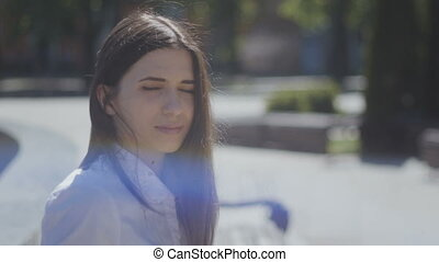 close up portrait of young woman in a white shirt on a sunny day in the street of city