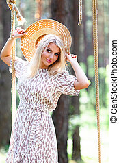 Close up portrait of young woman in straw hat sitting on a rope swing