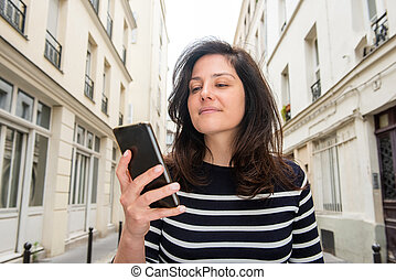 Close up portrait of young woman looking at mobile phone in city