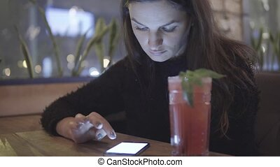 Close up portrait of young woman using her smart phone and drinking coctail.