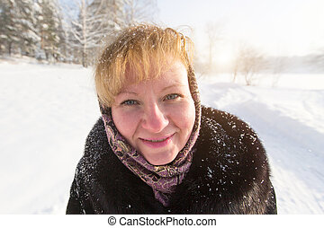 Close-up portrait of young woman winter snow outdoors.