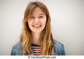 Close up portrait of young woman with long blond hair smiling by white background