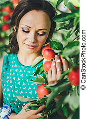 portrait of young woman with red apple in garden