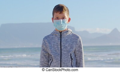 Close-up portrait view of a young boy on the beach on background table mountaine wearing a protective face mask to prevent Covid-19 Coronavirus pandemic.