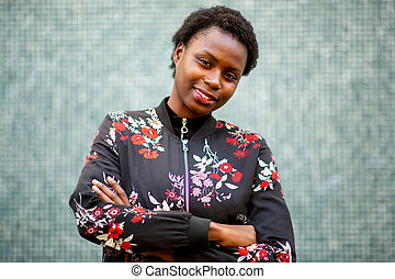 young african woman smirking with arms crossed