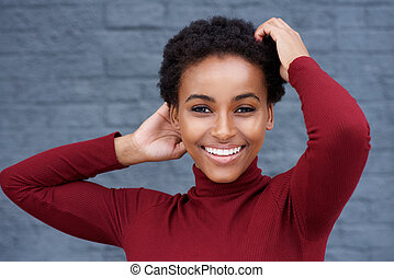 young smiling woman with hand in hair