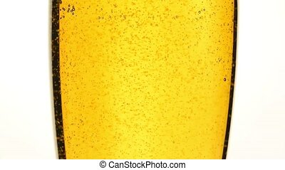 Close up pouring beer with bubbles in glass