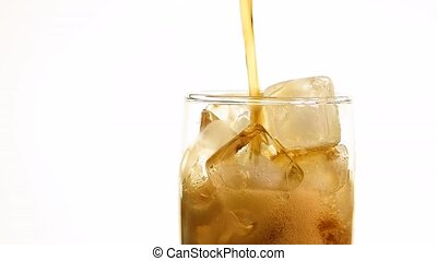 Close up pouring cola on ice cubes in glass - Extreme close...