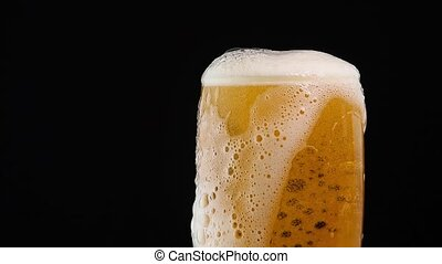 Close up pouring lager beer in glass over black