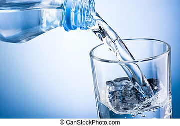 Close-up pouring water from bottle into glass on a blue...