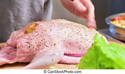 Close-up preparation of duck or goose for baking. Sprinkle...