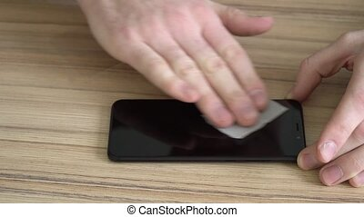 Close-up. Preparing the screen for a new mobile phone. Cleaning with a damp cloth. New protective, chopped, shockproof glass.