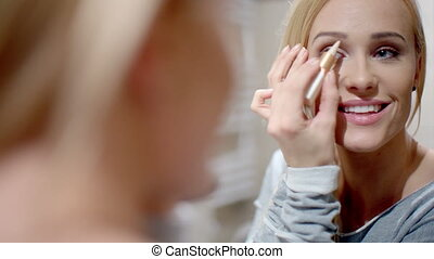 Pretty Blond Woman Applying Eyebrow Makeup