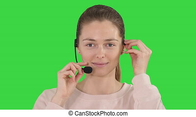 Pretty female support center operator with headset smiling to camera on a Green Screen, Chroma Key.