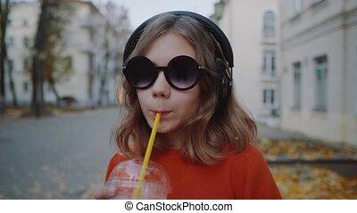Close up Pretty hipster teen listen music in headphones,...