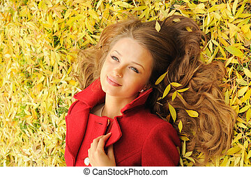 Close up pretty woman portrait lying on yellow maple leaves