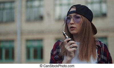 Close up pretty young hipster woman in black cap vape ecig. ...