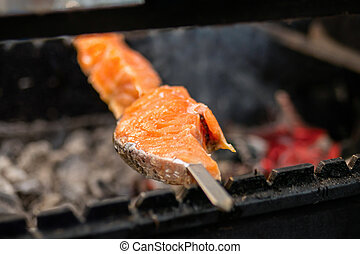 Close up - process of cooking salmon skewers on grill - street food concept