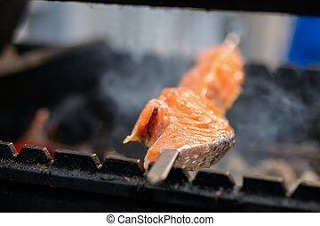 Close up: process of cooking salmon skewers on grill - street food concept