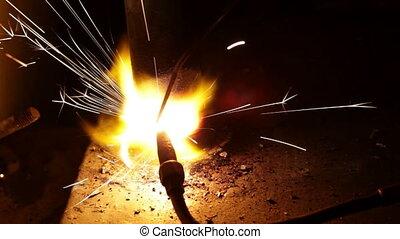 Close up process of welding metals in darkness -...