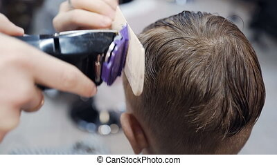 Close up. Professional hairdresser doing a new haircut on...