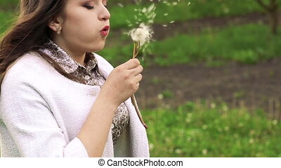 Close up profile of  young girl blowing dandelion in the garden. Slowly