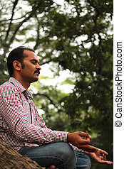 Close-up profile photo of a handsome indian businessman meditating under a tree in a garden. The person is sitting in lotus posture and is composed, relaxed closing his eyes for better concentration