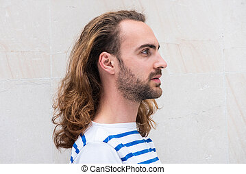 Close up profile young man with long hair and beard by white background