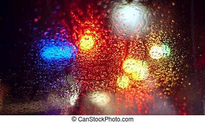 Close up rain drops on car window glass with blurred night...