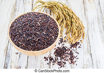 Close up raw purple Rice berry in wooden bowl on wooden background