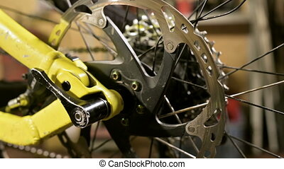 Close-up rear wheel brake disc rotates in a bicycle repair...