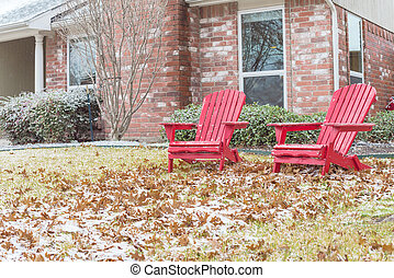 Close-up red adirondack chairs with snow covered at front porch of suburbs house in Texas, USA