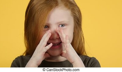 Close-up red-haired child screaming putting his hands to his...