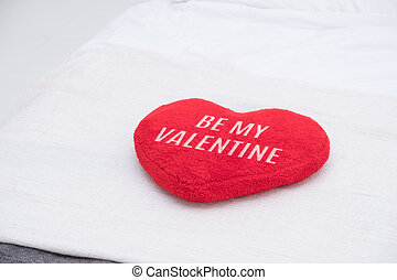 Close up red heart pillow with be my valentine word lying on bed blanket in white bedroom. Love romance concept.