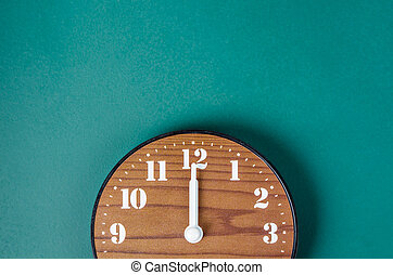 Close up retro clock on green board background.
